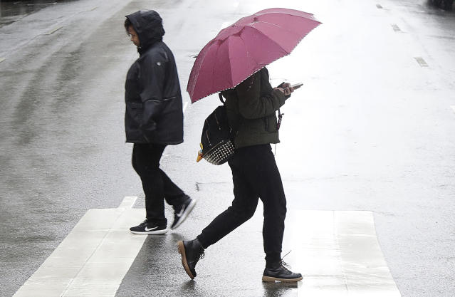 Pedestrians cross Pine street in San Francisco, Tuesday, Jan. 15, 2019. The first in a series of Pacific storms brought heavy rain to Southern California and snow in the mountains Monday, closing some highways and snarling traffic. (AP Photo/Jeff Chiu)