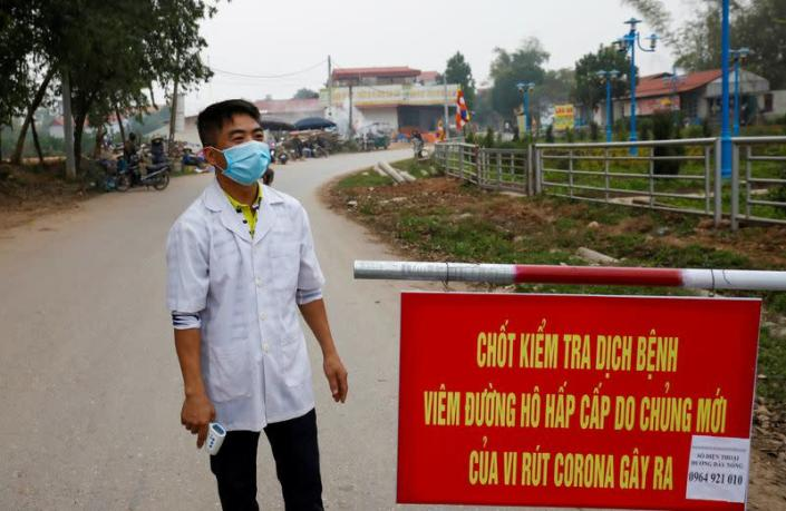 A Vietnamese health worker stands guard at a disease checkpoint of Son Loi commune in Vinh Phuc province