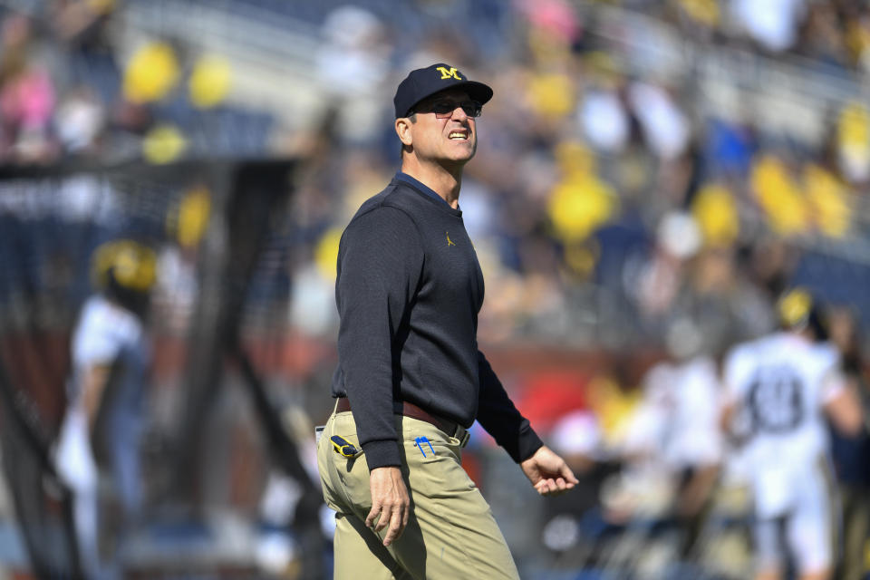 Jim Harbaugh walks on the sideline prior to a game.