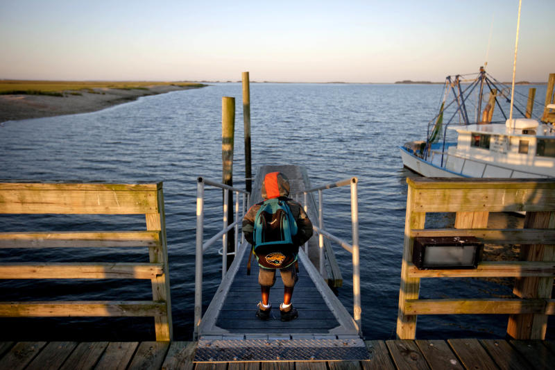 Jonathan Wilson, 6, stands on the dock before boarding a ferry from his home in the Hog Hammock community of Sapelo Island, Ga. to the mainland to attend school on Wednesday, May 15, 2013. (AP Photo/David Goldman)