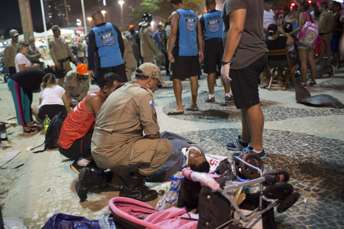 <p>Firefighter gives the first aid to a man that was hurt after a car drove into the crowded seaside boardwalk along Copacabana beach in Rio de Janeiro, Brazil, Thursday, Jan. 18, 2018. (Photo: Silvia Izquierdo/AP) </p>