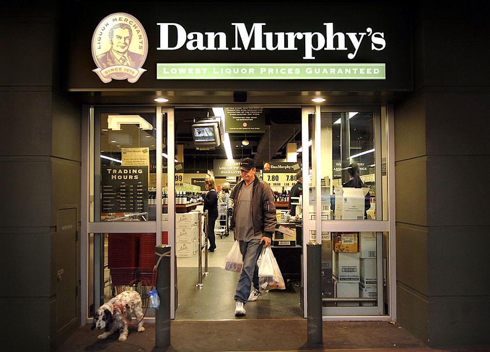 A man and a dog walk out of a Dan Murphy's store.