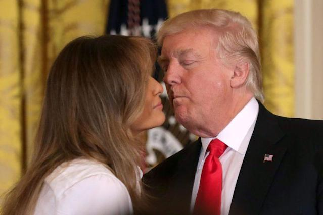 First lady Melania Trump and President Trump share a kiss at the White House on Friday. (Photo: Getty Images)