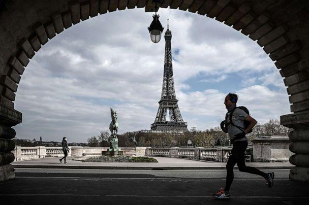 PHOTO: A man jogs on the Bir-Hakeim bridge in front of the Eiffel Tower in Paris on April 2, 2020, during the lockdown in France to stop the spread of COVID-19 (novel coronavirus). (Philippe Lopez/AFP via Getty Images)