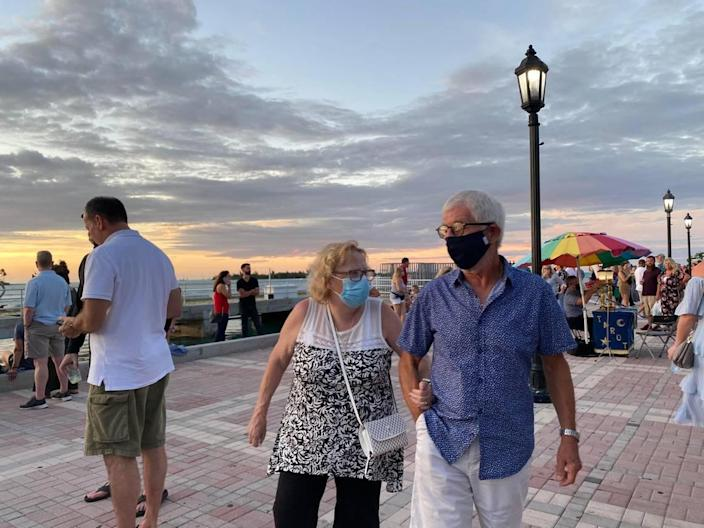 A couple walks through Mallory Square in Key West during Sunset Celebration.