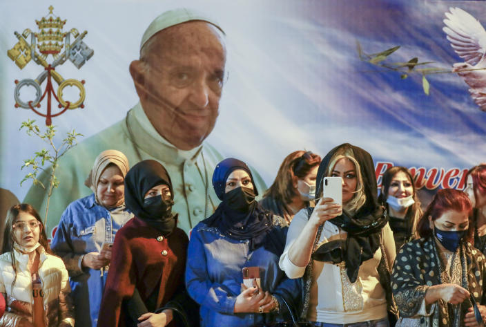 Women wait outside the Chaldean Cathedral of Saint Joseph, in Baghdad, Iraq, Saturday, March 6, 2021, where Pope Francis, depicted on a giant poster at their back, is concelebrating a mass. Earlier today Francis met privately with the country's revered Shiite leader, Grand Ayatollah Ali al-Sistani. (AP Photo/Andrew Medichini)
