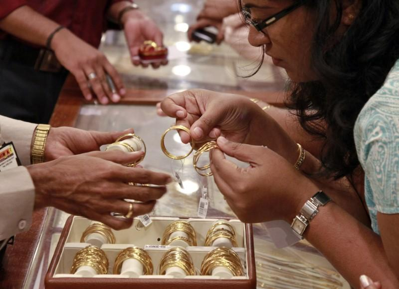 Customer looks at bangles before purchasing them at a gold showroom in the southern Indian city of Kochi