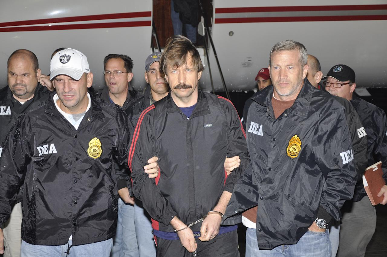 This image provided by the Drug Enforcement Administration shows Russian arms trafficking suspect Viktor Bout, center, in U.S. custody after being flown from Bangkok to New York on Tuesday Nov. 16, 2010 in a chartered U.S. plane, extradited in manacles to face terrorism charges despite a final outraged push by Russian diplomats to persuade Thailand to release him.