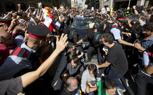 <p>Pro-independence demonstrators try to stop the car carrying Xavier Puig, a senior at the Department of External Affairs, Institutional Relations and Transparency of the Catalan Government office, after he was arrested by Guardia Civil officers in Barcelona, Spain, Wednesday, Sept. 20, 2017. (Photo: Emilio Morenatti/AP) </p>