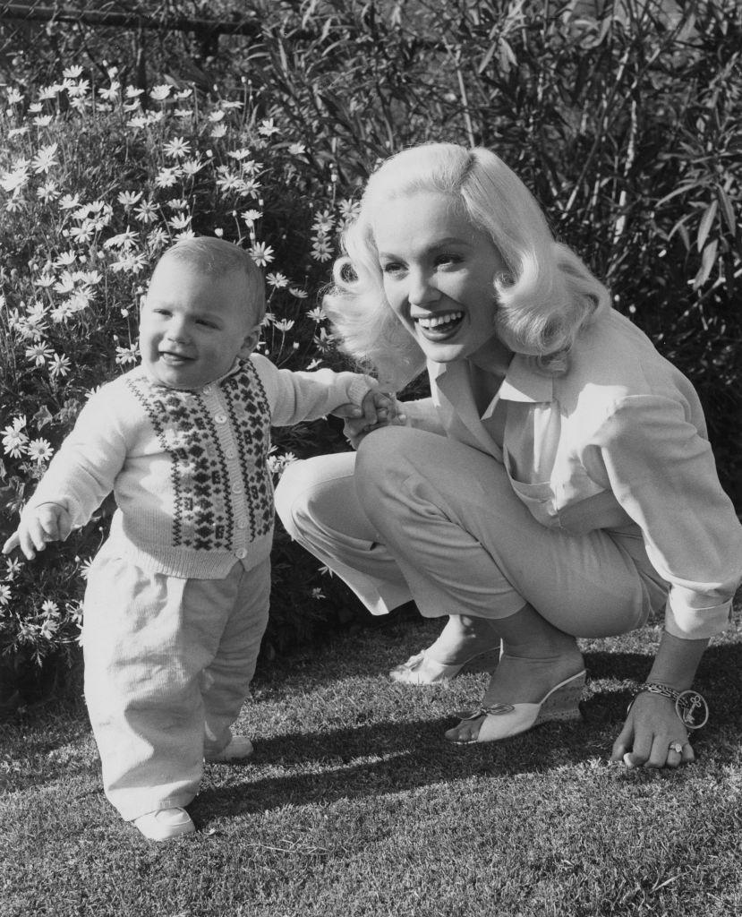 <p>Mamie wears a casual button-down and jeans in her home garden with her 11-month-old son. The actress and her husband, bandleader Ray Anthony, welcomed Perry Anthony in 1956. </p>