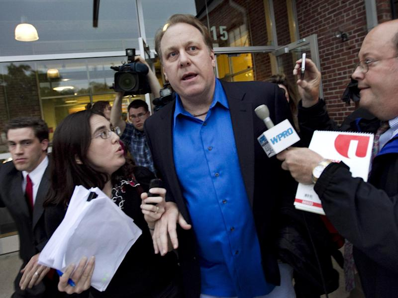 FILE- In this May 21, 2012, file photo, former Boston Red Sox pitcher Curt Schilling, center, is followed by members of the media as he departs the Rhode Island Economic Development Corporation headquarters in Providence, R.I. Schilling has dabbled in politics, World War II history and raised millions for Lou Gehrig's disease, but it's a gamble on his video game company 38 studios that is in danger of failing and possibly leaving Rhode Island taxpayers with the tab on a $75 million loan guarantee that lured the firm from Massachusetts in 2010. (AP Photo/Steven Senne, File)