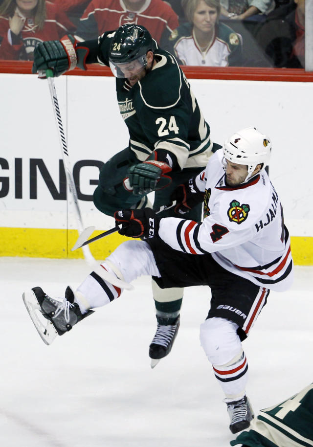 Minnesota Wild left wing Matt Cooke (24) and Chicago Blackhawks defenseman Niklas Hjalmarsson (4), of Sweden, collide during the third period of Game 4 of an NHL hockey second-round playoff series in St. Paul, Minn., Friday, May 9, 2014. The Wild won 4-2. (AP Photo/Ann Heisenfelt)