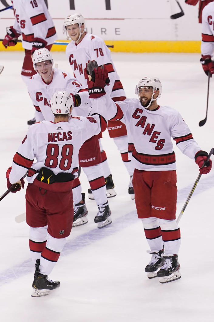 Carolina Hurricanes center Martin Necas (88) is congratulated by his teammates after he scored the winning goal in a shootout at an NHL hockey game against the Florida Panthers, Saturday, Feb. 27, 2021, in Sunrise, Fla. The Hurricanes defeated the Panthers 4-3. (AP Photo/Marta Lavandier)