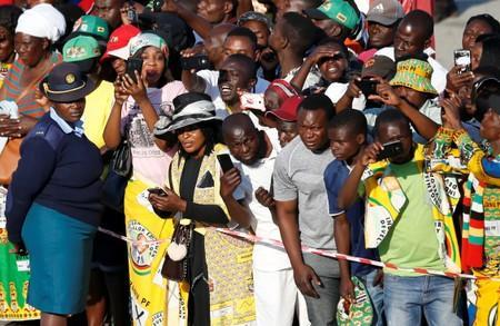 Zimbabweans look on as the body of former Zimbabwean President Robert Mugabe is transported to his home after arriving back in the country from Singapore, in Harare