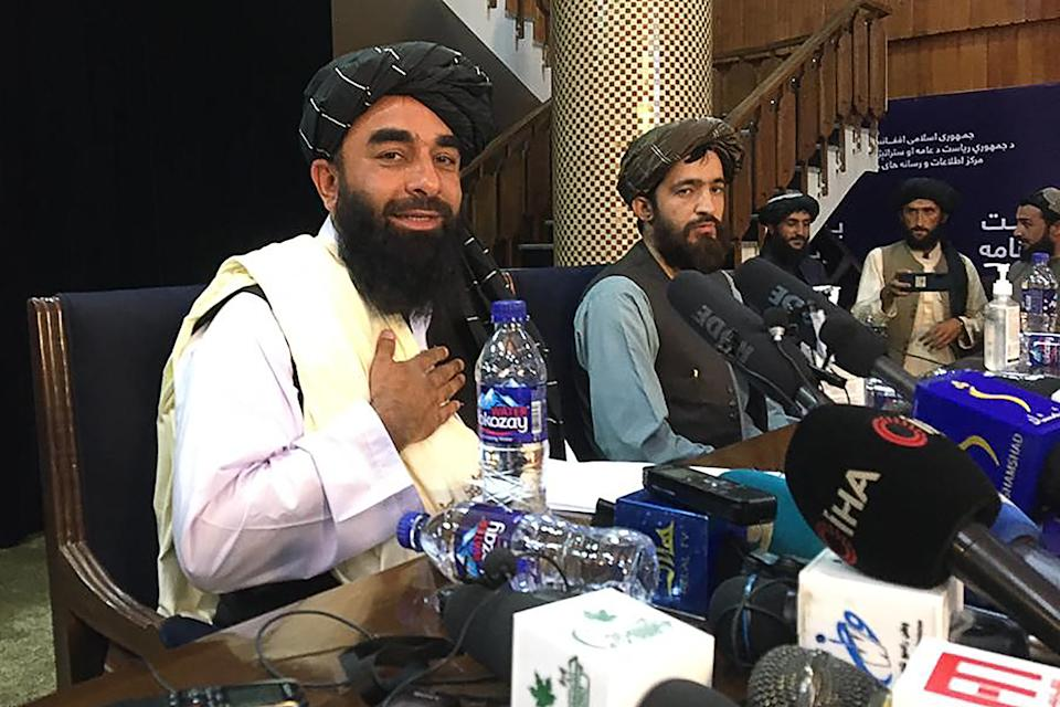 Taliban spokesperson Zabihullah Mujahid (L) gestures as he arrives to hold the first press conference in Kabul on August 17, 2021 following the Taliban stunning takeover of Afghanistan. (Photo by Hoshang HASHIMI / AFP) (Photo by HOSHANG HASHIMI/AFP via Getty Images)