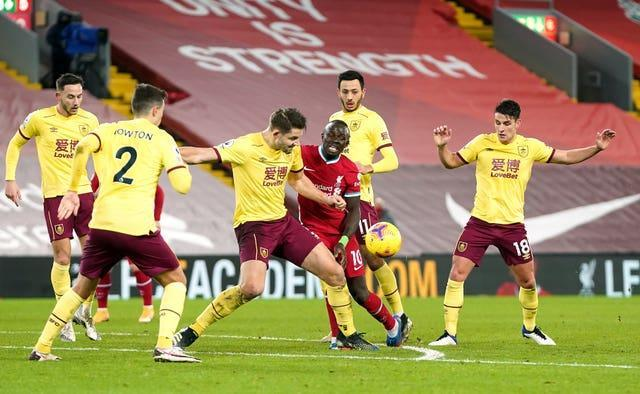 James Tarkowski tackles Liverpool forward Sadio Mane surrounded by other Burnley players