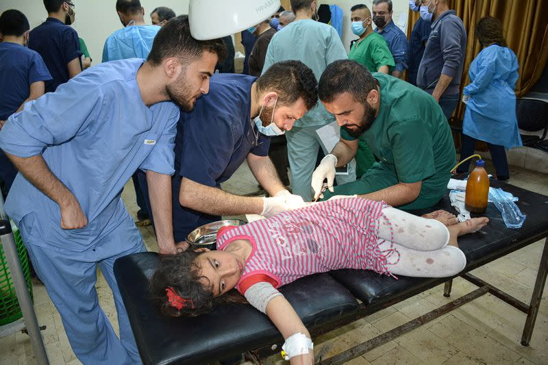 An injured girl is treated after pre-dawn raids on the Mediterranean port region of Latakia