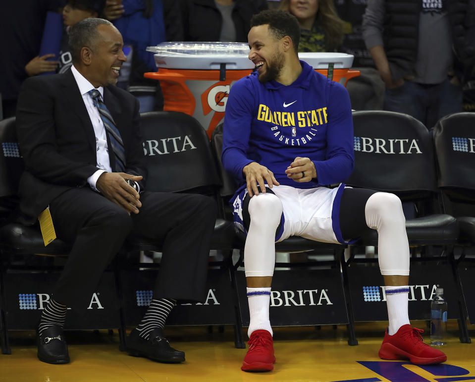 Warriors star Stephen Curry and his father, former Hornets guard Dell Curry, share a laugh before a game between the two teams. (AP)