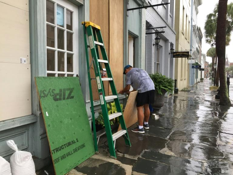 A man boards up a jewelry store on Broad Street in Charleston, South Carolina (AFP Photo/Lucie AUBOURG)