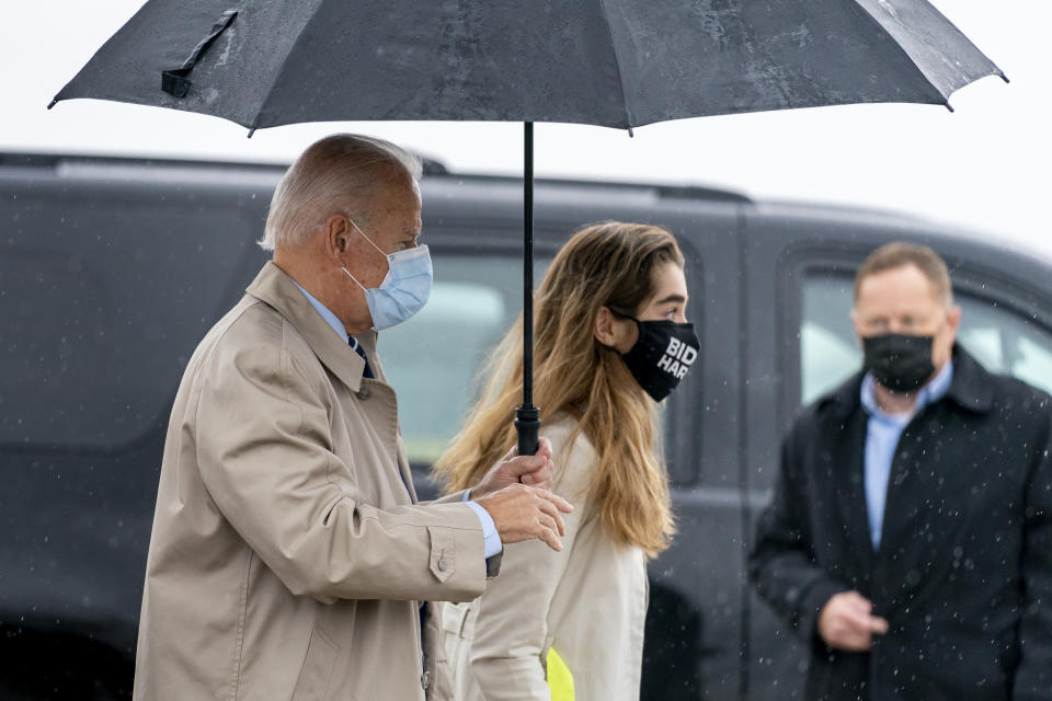 Democratic presidential candidate former Vice President Joe Biden, accompanied by his granddaughter Natalie Biden, right, boards his campaign plane at New Castle Airport in New Castle, Del., Thursday, Oct. 29, 2020, to travel to Florida for drive-in rallies. (AP Photo/Andrew Harnik)