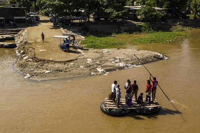 Migrants and residents use a makeshift raft to cross the Suchiate river from Tecun Uman in Guatemala to Ciudad Hidalgo in southern Mexico (AFP Photo/Pedro PARDO)
