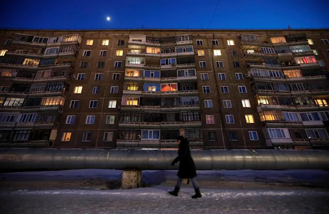 """A woman walks past an apartment in the town of Aksu, north-eastern Kazakhstan, February 22, 2018. REUTERS/Shamil Zhumatov SEARCH """"AKSU"""" FOR THIS STORY. SEARCH """"WIDER IMAGE"""" FOR ALL STORIES. TPX IMAGES OF THE DAY."""