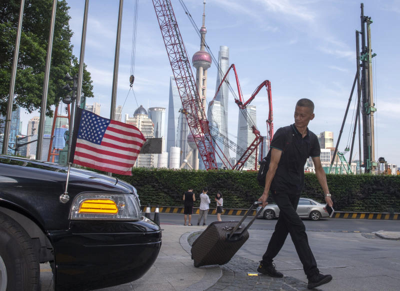 FILE - In this July 30, 2019, file photo, a traveller pulls a trolley past a U.S. embassy car outside a hotel in Shanghai. China has announced it will raise tariffs on $75 billion of U.S. products in retaliation for President Donald Trump's planned Sept. 1 duty increase in a war over trade and technology policy. (AP Photo/Ng Han Guan, File)