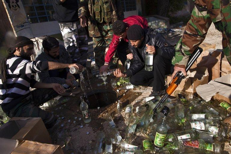 Syrian rebels empty bottles of alcohol in a drain in the northern city of Aleppo on December 28, 2012