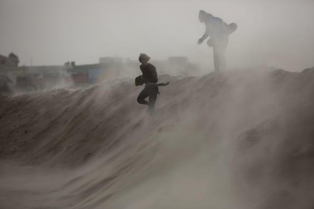 <p>Kids play on man-made sand hill to block high waves ahead of the upcoming storm in Tel Aviv's beach front, Israel, Jan. 6, 2015. (Photo: Oded Balilty/AP) </p>