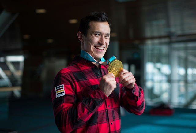 FILE - In this Feb. 26, 2018, file photo, figure skater Patrick Chan, of Canada, holds his 2018 Olympic gold medal after arriving from South Korea at Vancouver International Airport in Richmond, B.C. Chan, who won his long-awaited Olympic gold as part of the team event at the Pyeongchang Olympics, is retiring after more than a decade on the world stage. Chan made his decision official Monday, April 16, 2018, after alluding to it during the Winter Games. (Darryl Dyck/The Canadian Press via AP, File)