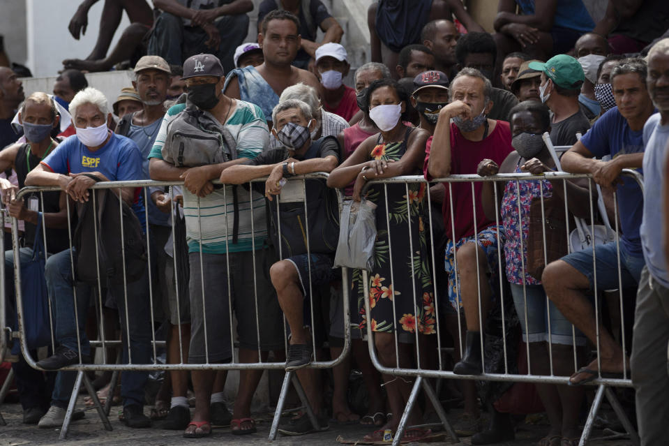 People wait in line for a meal donated by the Leao Xlll Foundation amid the COVID-19 pandemic in Rio de Janeiro, Brazil, Wednesday, April 7, 2021. (AP Photo/Silvia Izquierdo)