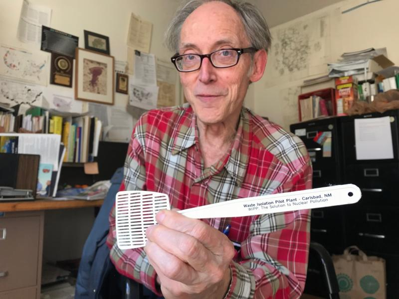 In this March 5, 2019 photo, Don Hancock with the Southwest Research and Information Center holds up a promotional flyswatter advertising the Waste Isolation Pilot Plant as the solution to nuclear pollution while in his office in Albuquerque, New Mexico. Hancock is among the watchdogs who have been monitoring the federal nuclear waste repository for decades. (AP Photo/Susan Montoya Bryan)
