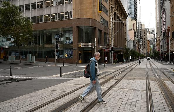A man wears a mask on a near-deserted street in the central business district as people stay home due to the COVID-19 novel coronavirus outbreak in Sydney.