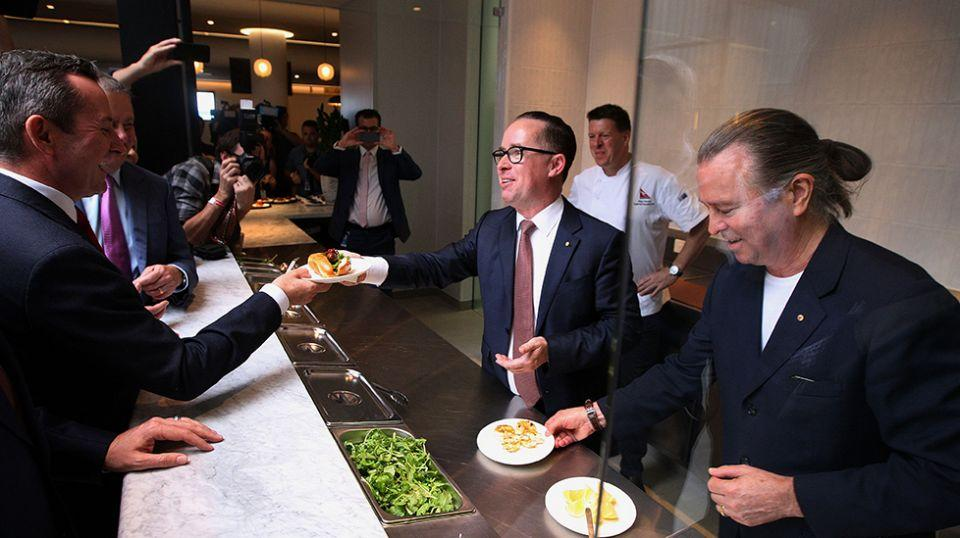 Qantas CEO Alan Joyce, centre, and chef Neil Perry, right, serve food to attendees during a media event ahead of the flight. Source: Getty