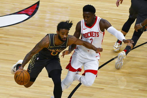 Chicago Bulls guard Coby White, left, drives with the ball against Houston Rockets guard Victor Oladipo, right, during the first half of an NBA basketball game Monday, Jan. 18, 2021, in Chicago. (AP Photo/Matt Marton)