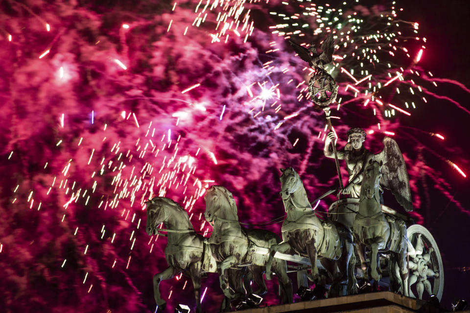 Fireworks light the sky above the Quadriga at the Brandenburg Gate during New Year celebrations in Berlin, Germany, Wednesday, Jan. 1, 2020. Hundred thousands of people celebrated New Year's Eve welcoming the new year 2020 in Germany's capital. (Christophe Gateau/dpa via AP)