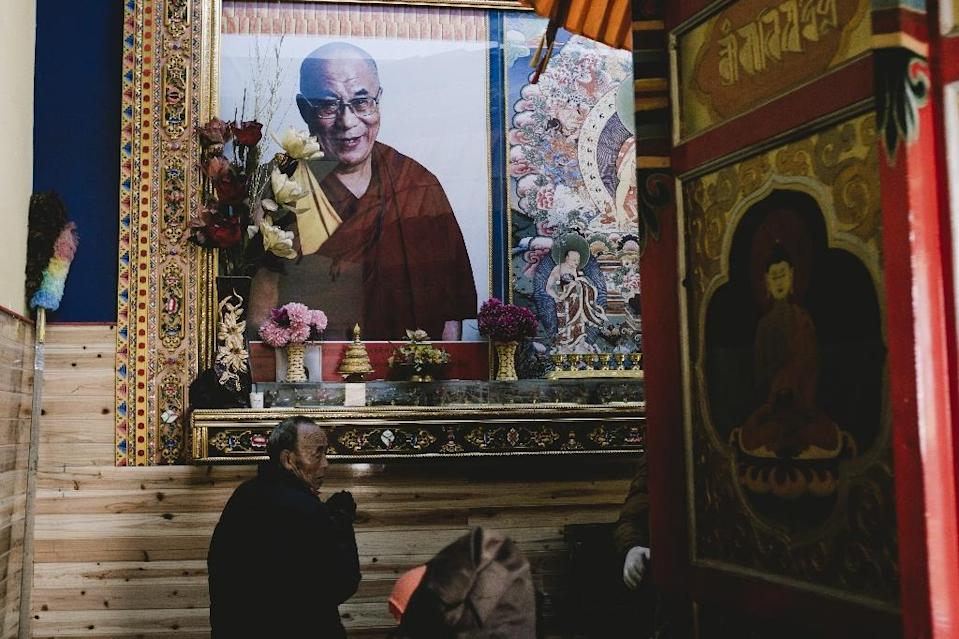 A man prays below a portrait of the Dalai Lama at Kirti Monastery in Aba, a Tibetan area of China's Sichuan province, on December 9, 2015 (AFP Photo/Benjamin Haas)