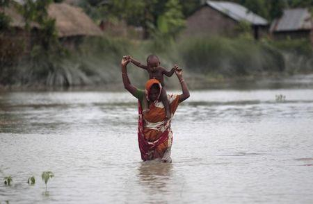 A woman carries her child as she wades through floodwaters at a flooded village in Gaibandha
