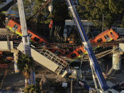 An aerial view of subway cars dangle at an angle from a collapsed elevated section of the metro, in Mexico City, Tuesday, May 4, 2021. The elevated section collapsed late Monday killing at least 23 people and injuring at least 79, city officials said. (AP Photo/Fernando Llano)