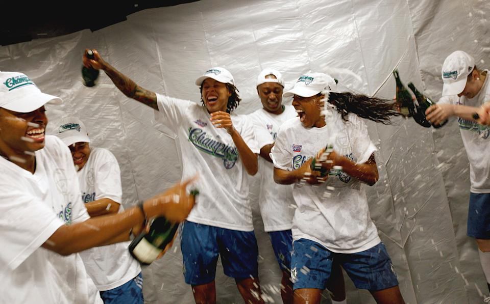Seimone Augustus, third from left, and her Minnesota Lynx teammates Charde Houston, center, and Monica Wright, celebrate in the locker room after the Lynx defeated the Atlanta Dream to complete a three-game sweep and win the 2011 WNBA championship. (AP Photo/David Goldman)