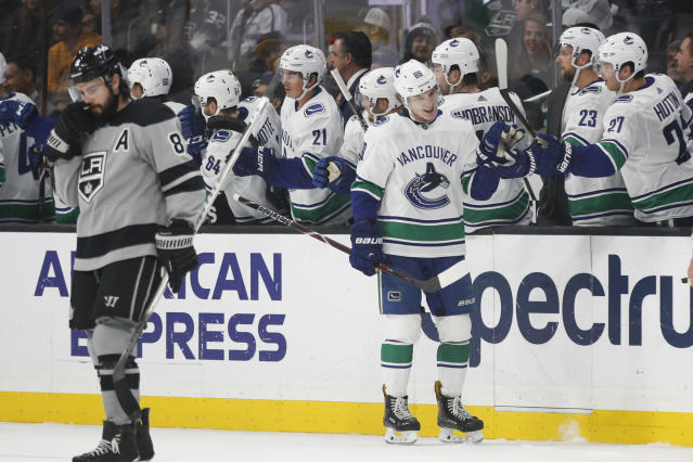 Vancouver Canucks' Adam Gaudette, center, celebrates his goal with teammates as Los Angeles Kings' Drew Doughty skates near them during the second period of an NHL hockey game Saturday, Nov. 24, 2018, in Los Angeles. (AP Photo/Jae C. Hong)