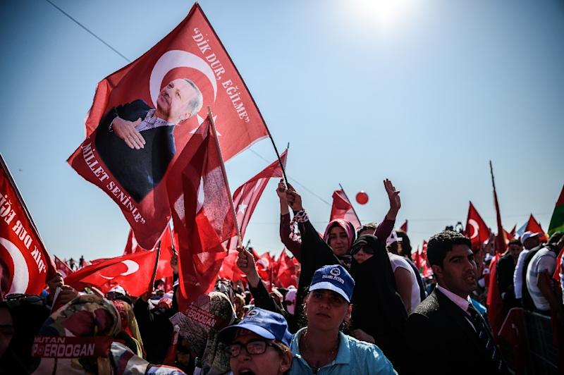 A demonstrator holds a flag picturing Turkish President Recep Tayyip Erdogan among demostrators wawing Turkish national flags and shout slogans on August 7, 2016 in Istanbul during a rally against failed military coup on July 15 (AFP Photo/Ozan Kose)