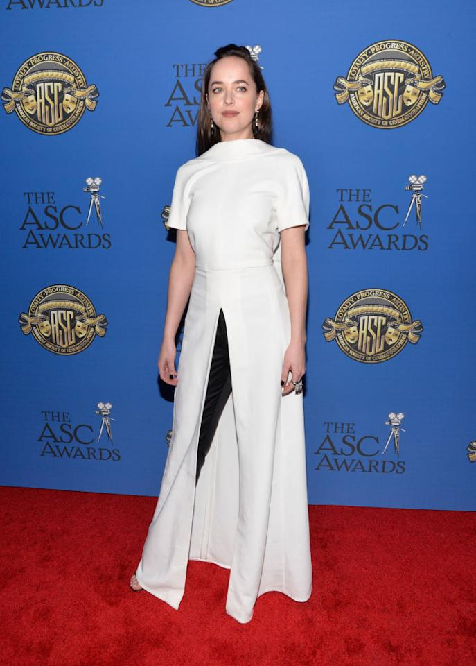 <p>Actress Dakota Johnson paired a short-sleeved white dress that featured an open back and a slit with black trousers at the 31st Annual American Society Of Cinematographers Awards in Los Angeles on February 4, 2017. She styled her hair in a topknot for the event. (Photo: Getty Images) </p>