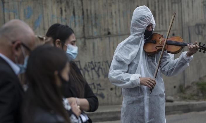 The violinist Antonio Hernández plays for the relatives of a Covid-19 victim at Serafin Cemetery in Bogota last week.
