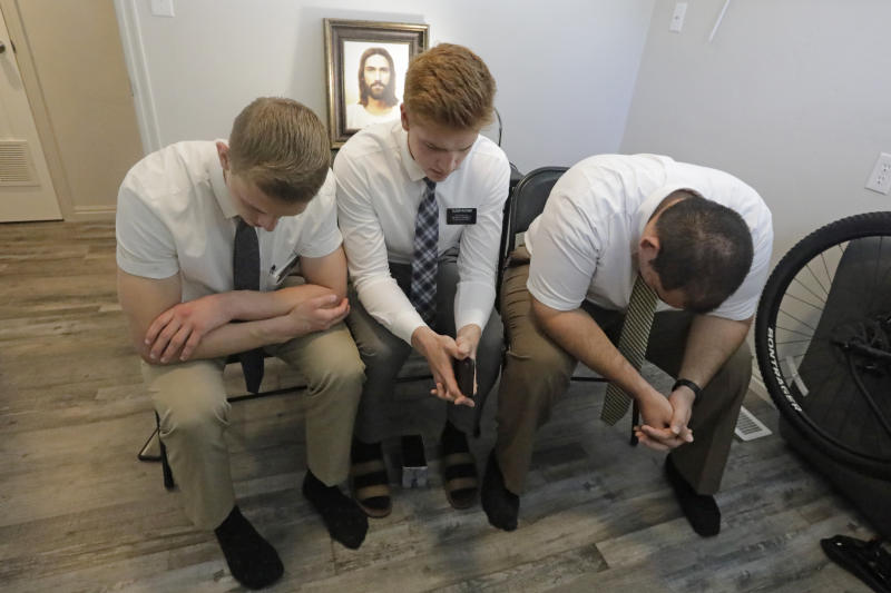 In this May 27, 2020, photo, missionaries with The Church of Jesus Christ of Latter-day Saints, from left to right, Andrew Zitting, Seth Rather, and Guenter Castrillo pray during a Zoom meeting with a local family while on a smartphone at their apartment, in Brigham City, Utah. After hastily bringing home 26,000 young men and women who were serving in foreign countries, the faith has begun sending many of them out again in their home countries with a new focus on online work that could stick even when the pandemic is over, church officials told The Associated Press. (AP Photo/Rick Bowmer)