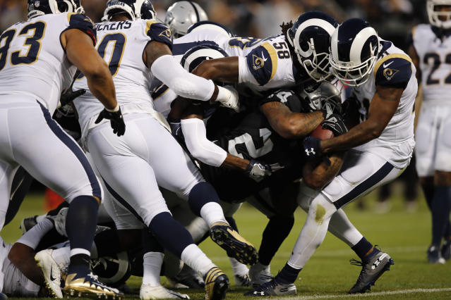Oakland Raiders running back Marshawn Lynch carries the ball into the end zone for a touchdown as Los Angeles Rams linebacker Cory Littleton (58) tries to stop him during the first half of an NFL football game against the Los Angeles Rams in Oakland, Calif., Monday, Sept. 10, 2018. (AP Photo/John Hefti)