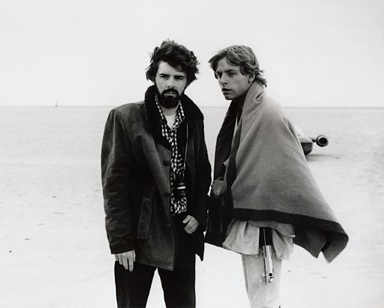 """In this March 1976 publicity photo released by Lucasfilm Ltd. & TM, director, George Lucas, and actor, Mark Hamill, who portrays young Luke Skywalker, are shown on the salt flats of Tunisia during principal photography of the original """"Star Wars."""" There's no mistaking the similarities. A childhood on a dusty farm, a love of fast vehicles, a rebel who battles an overpowering empire, George Lucas is the hero he created, Luke Skywalker. (AP Photo/Lucasfilm Ltd. & TM)"""