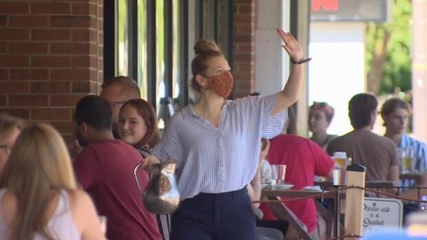 Staff at restaurants and pubs are free to remove masks for the first time in nearly a year, if employers allow it.  (Sam Martin/CBC - image credit)