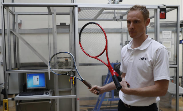 In this photo taken Friday June, 28, 2019, Jamie Caple-Davies, the head of the International Tennis Federation (ITF) science and technical department, holds up various designs of tennis racquets- both of which passed scrutiny by the ITF, at their lab in Roehampton, near Wimbledon south west London. Based for about 20 years in a three-room area on what used to be a pair of squash courts in Roehampton, the ITF tech lab is filled with more than $1 million worth of machines that help make sure rules are followed and parameters are met. (AP Photo/Alastair Grant)