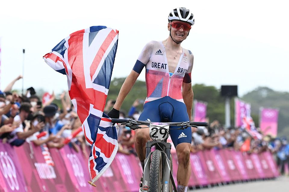 Britain's Thomas Pidcock celebrates as he crosses the finish to win the gold medal in the cycling mountain bike men's cross-country event during the Tokyo 2020 Olympic Games at the Izu MTB Course in Izu on July 26, 2021. (Photo by GREG BAKER / AFP) (Photo by GREG BAKER/AFP via Getty Images)
